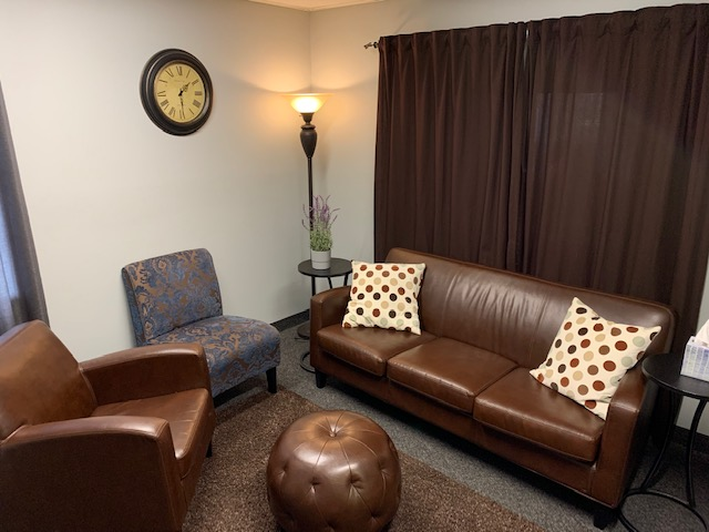 Adult therapy office with brown leather chair and couch.